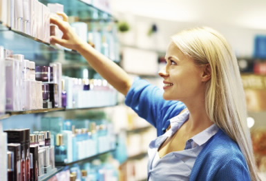 Image of female shopper selecting personal care/beauty products in a store.