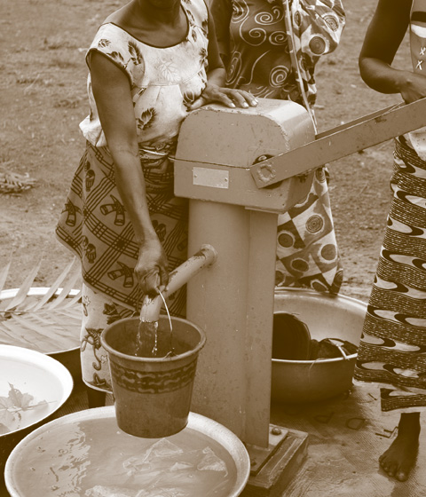 People operating hand operated water pump